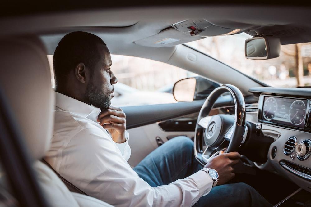 man in white dress shirt driving car during daytime