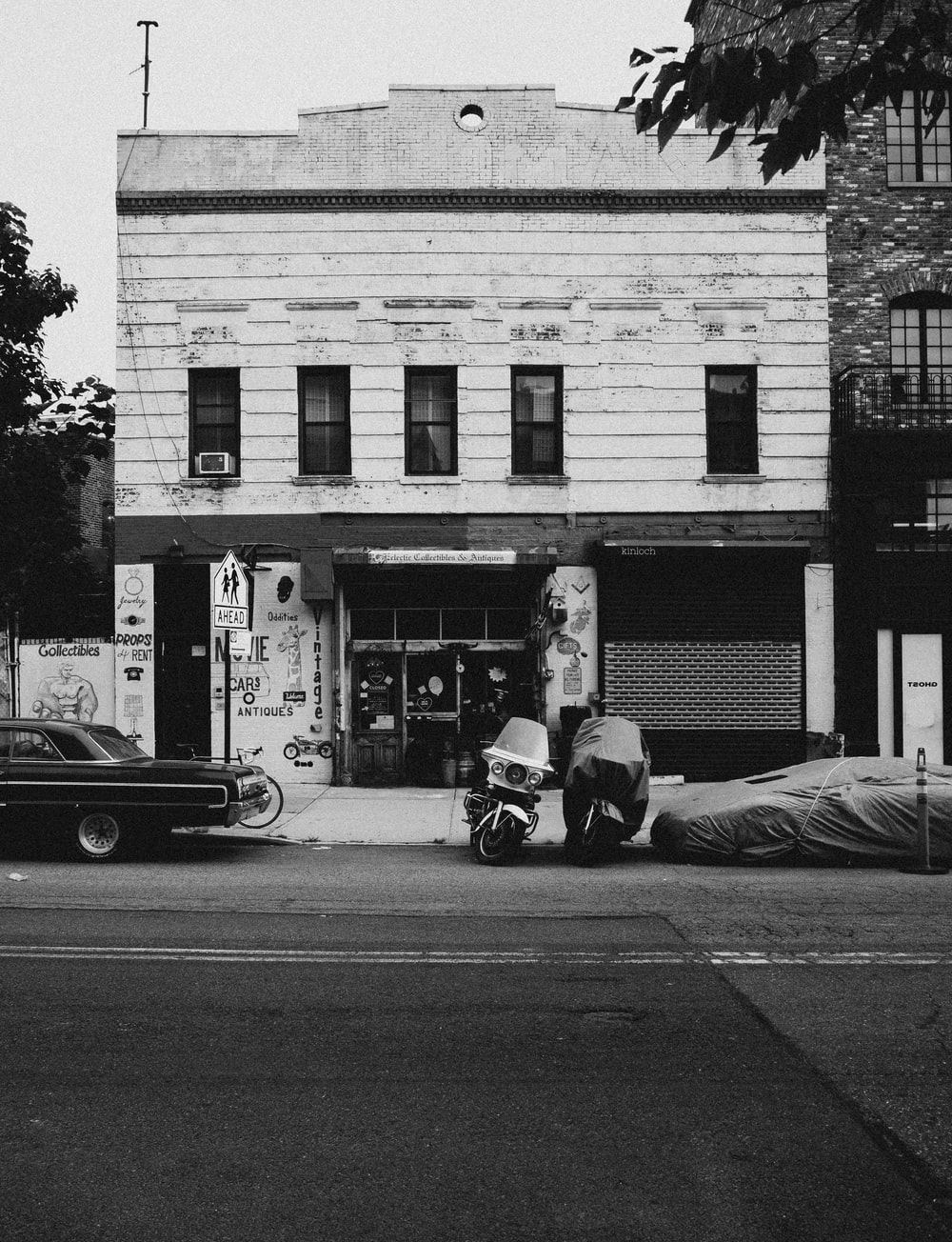 grayscale photo of man in black jacket and pants sitting on sidewalk near car parked beside