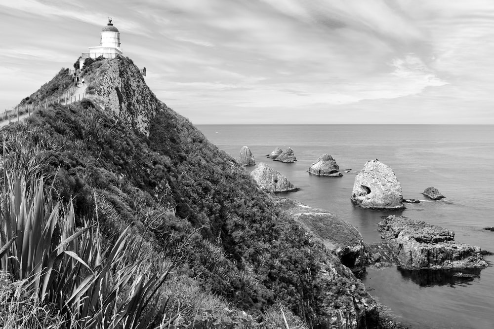 grayscale photo of lighthouse on rock formation near body of water