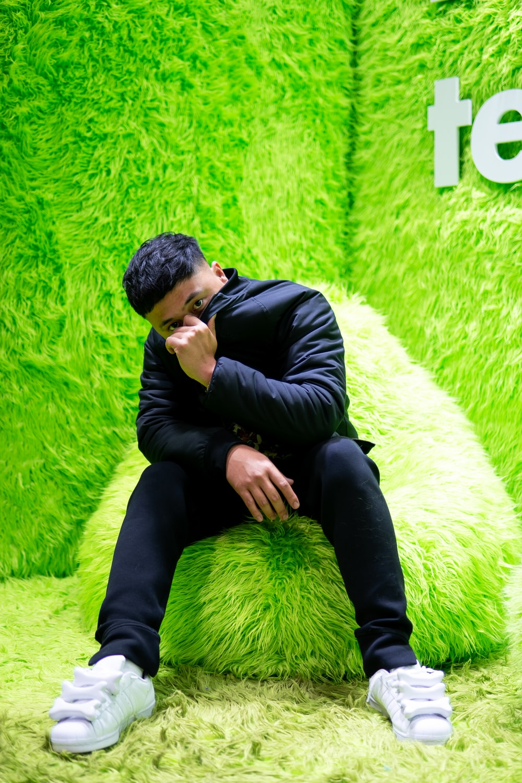 man in black long sleeve shirt and black pants sitting on green fur textile