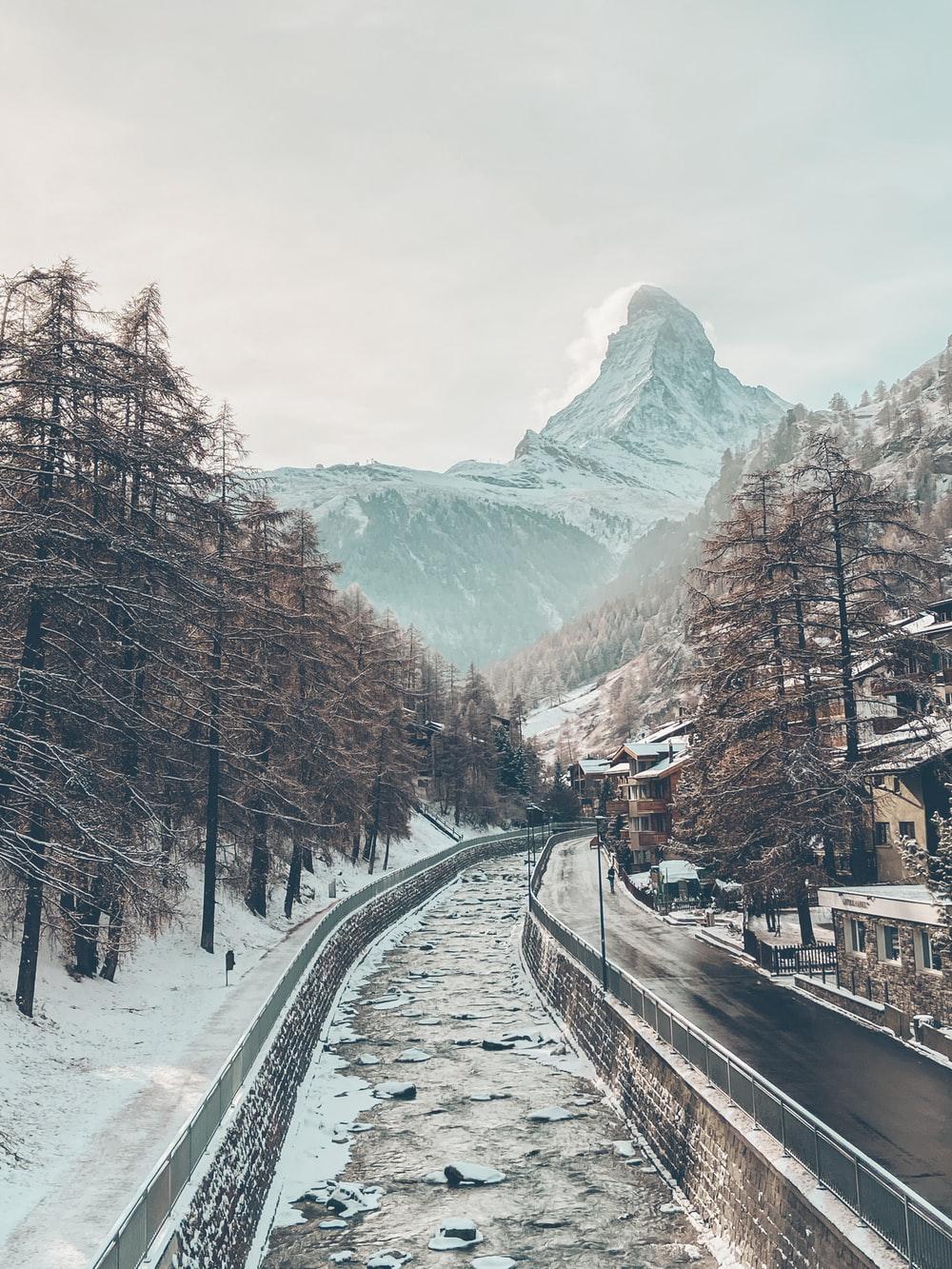 black train rail near trees and snow covered mountain during daytime