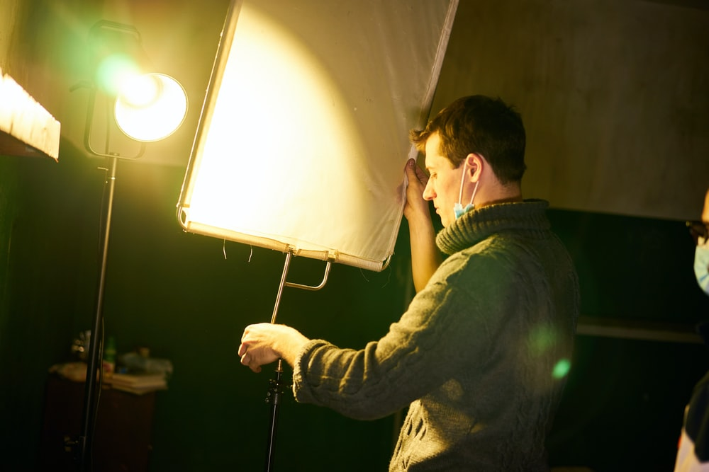 man in black jacket holding white and black floor lamp