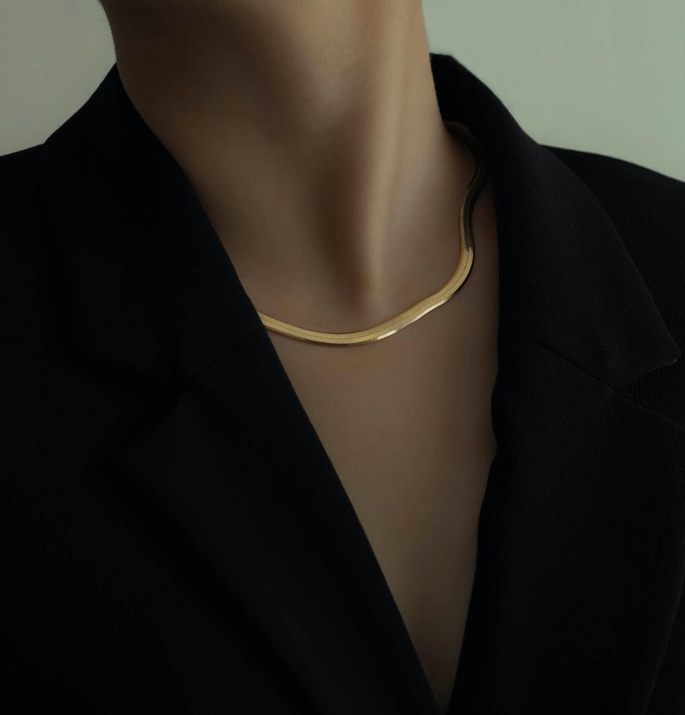 woman in black blazer wearing gold necklace