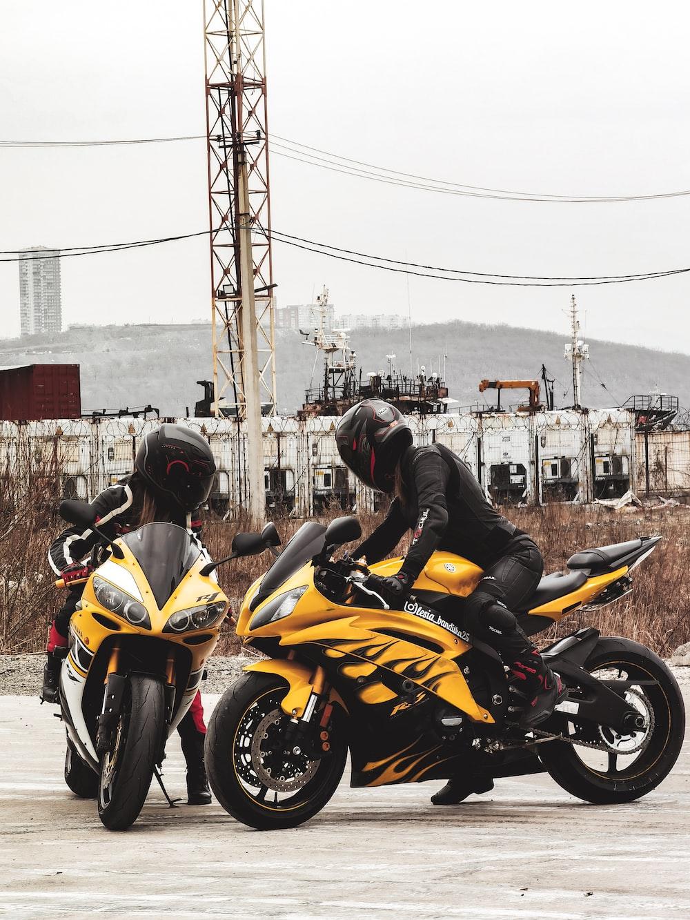 man in black helmet riding yellow sports bike during daytime