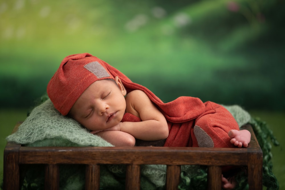 baby in red blanket lying on green textile
