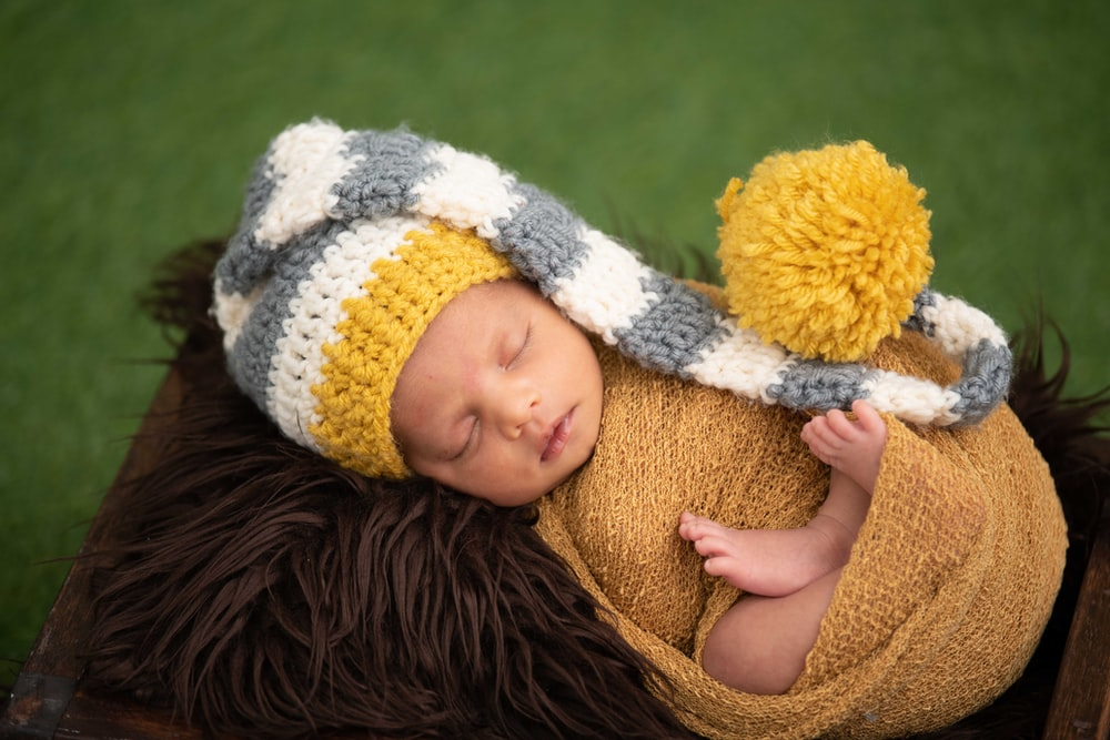 baby in white and black knit cap lying on brown textile