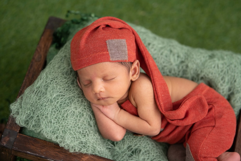 baby in red knit cap lying on gray textile
