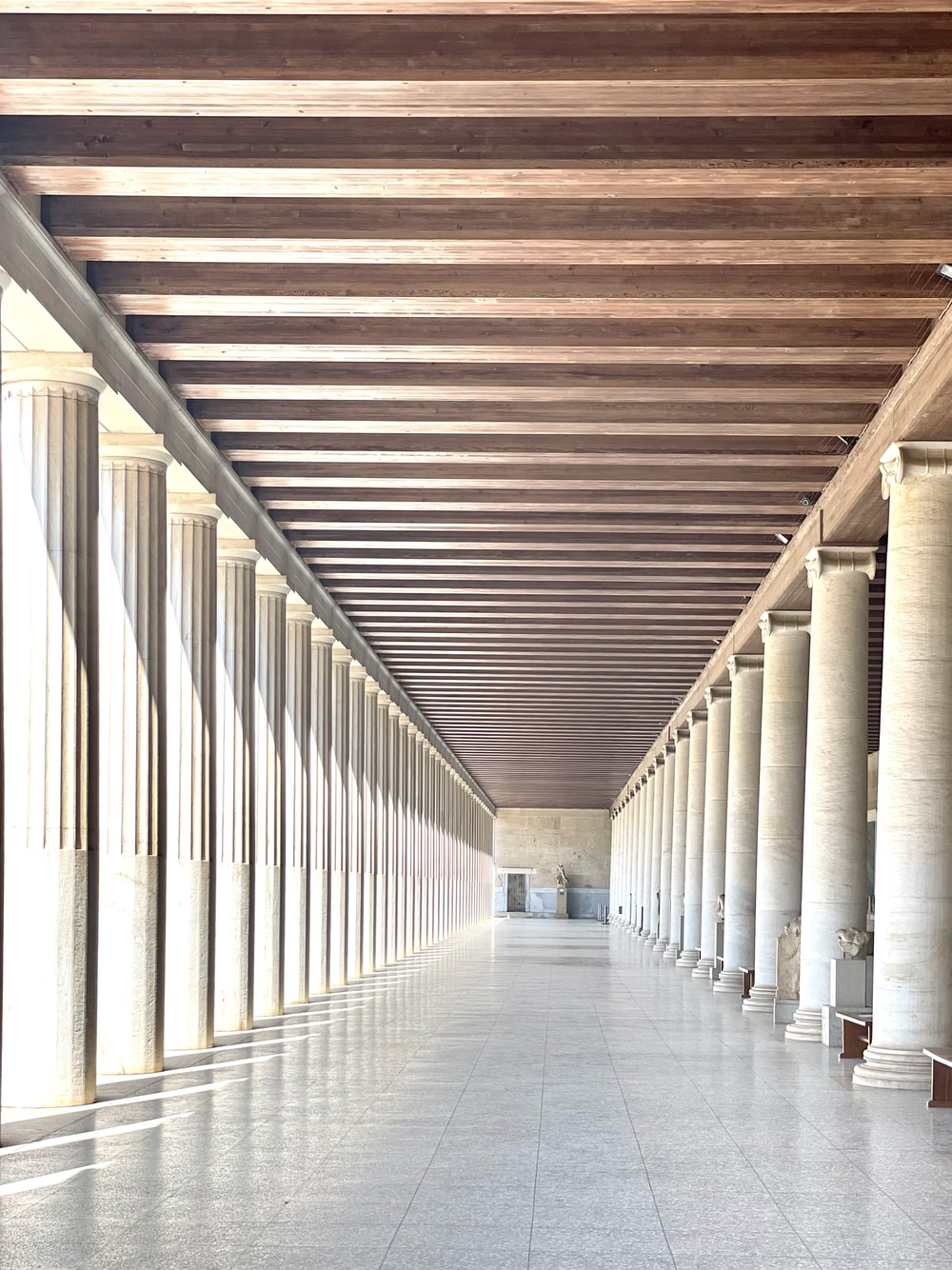 white and brown hallway with white columns