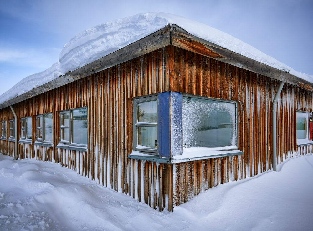 brown wooden house covered with snow during daytime
