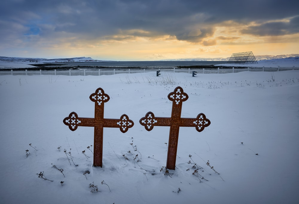 brown wooden cross on snow covered ground during daytime