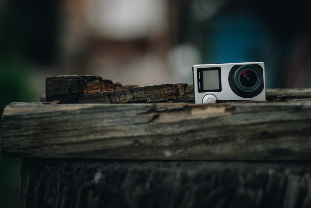 white and black camera on brown wooden surface