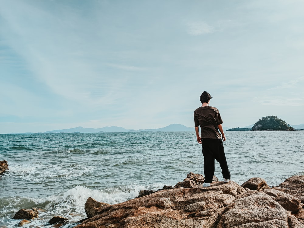 man in black jacket standing on brown rock near body of water during daytime