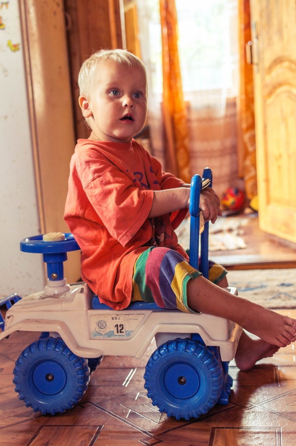 boy in red polo shirt sitting on white and blue plastic toy car