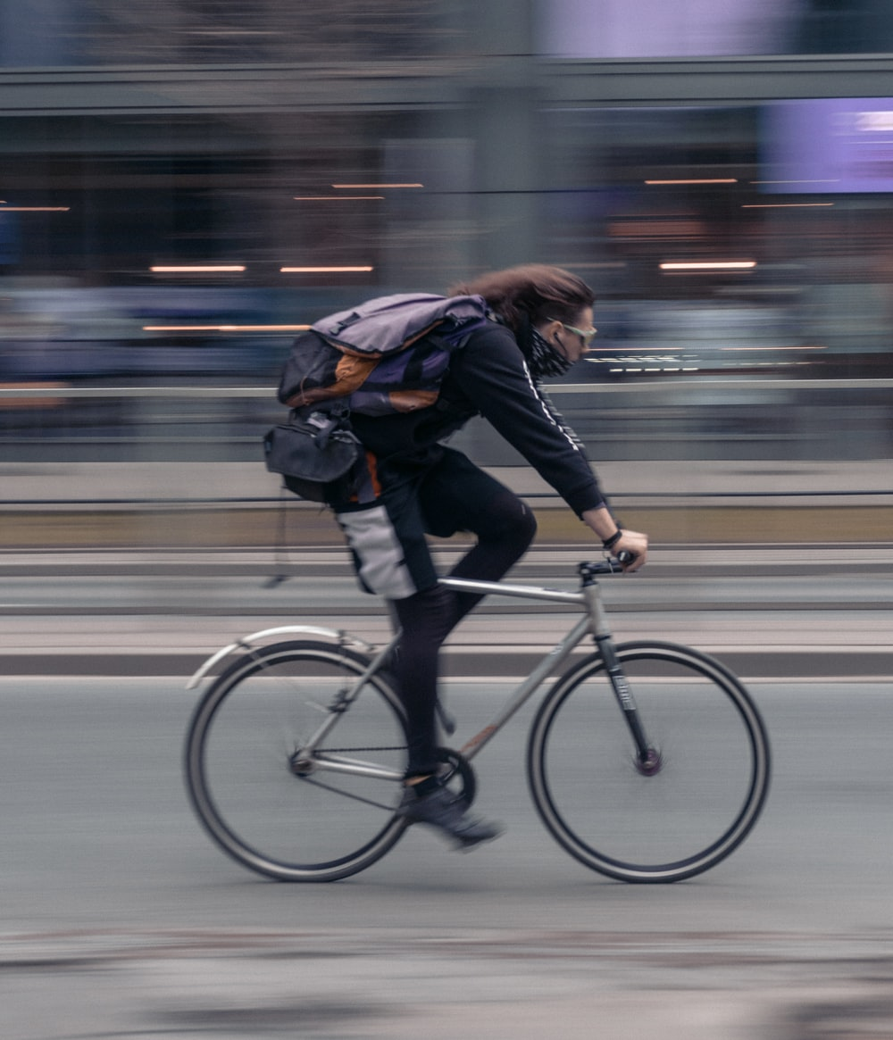 woman in black jacket riding on bicycle