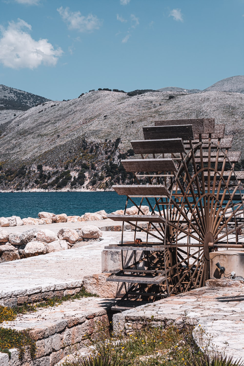 brown wooden stairs on rocky shore near body of water and mountain during daytime