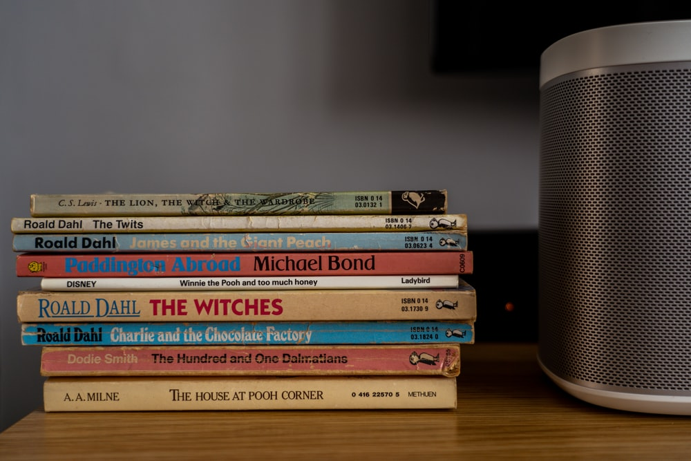 stack of books on brown wooden table