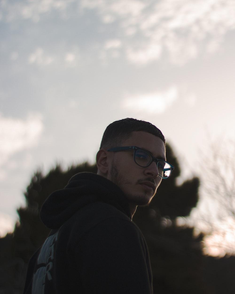 man in black hoodie wearing black sunglasses