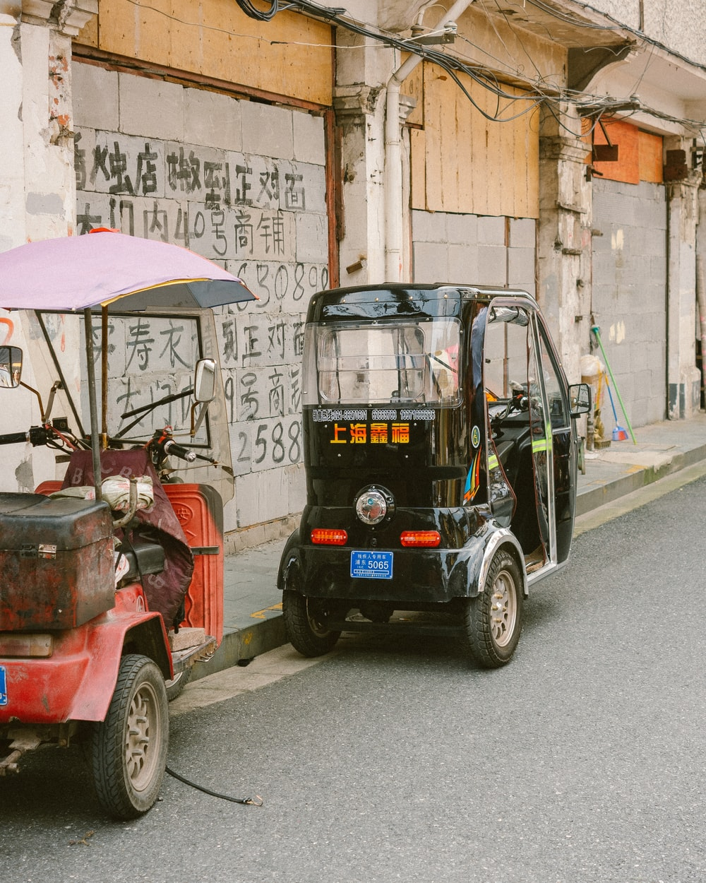 red and black auto rickshaw parked beside brown concrete building during daytime
