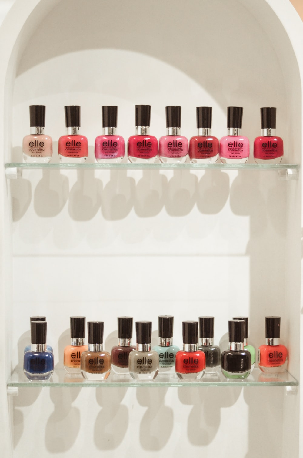 assorted nail polish bottles on white shelf