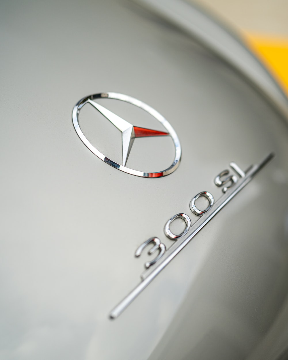 silver mercedes benz emblem on white surface