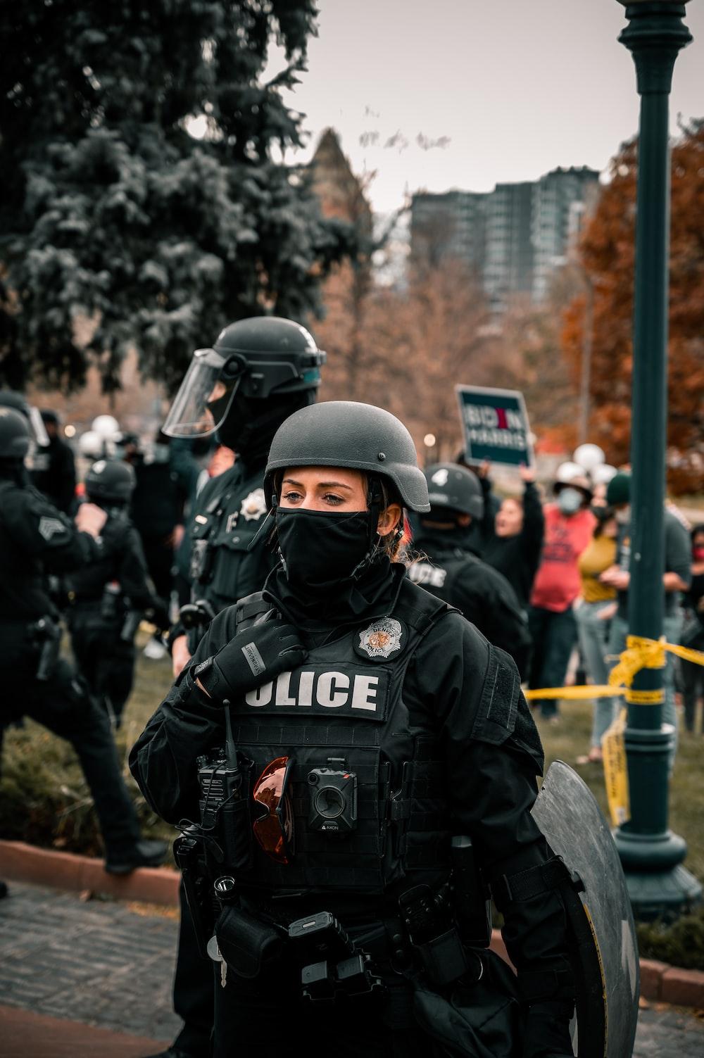 man in black helmet and black jacket standing near people during daytime