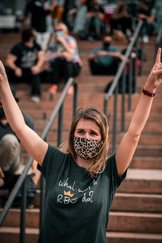 woman in black crew neck t-shirt raising her hands