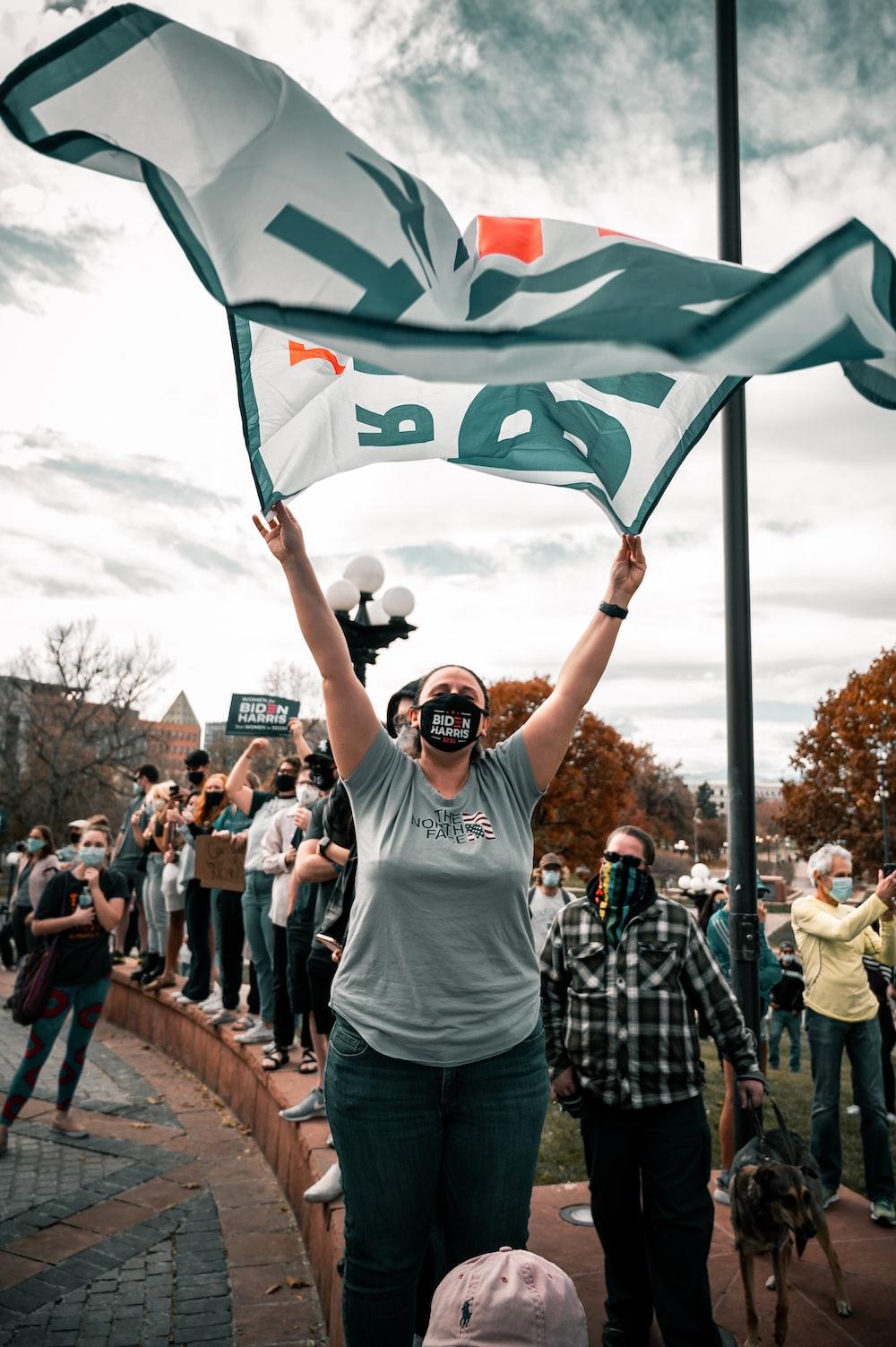 man in white crew neck t-shirt holding green flag