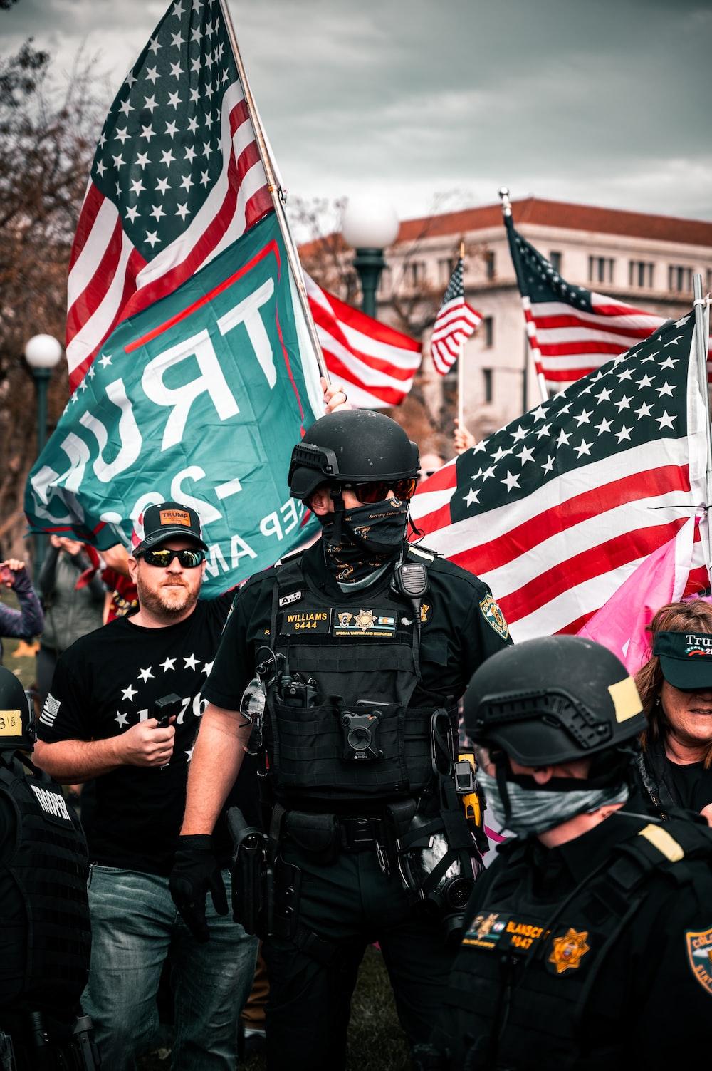 man in black police uniform holding us a flag
