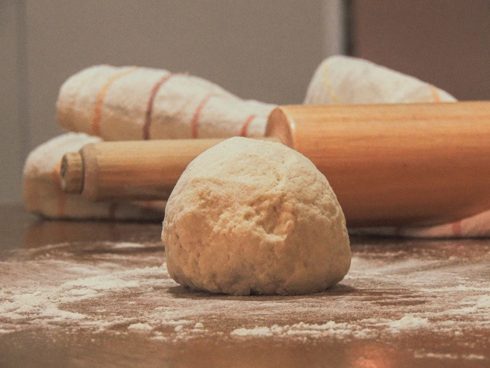 white dough on brown wooden table