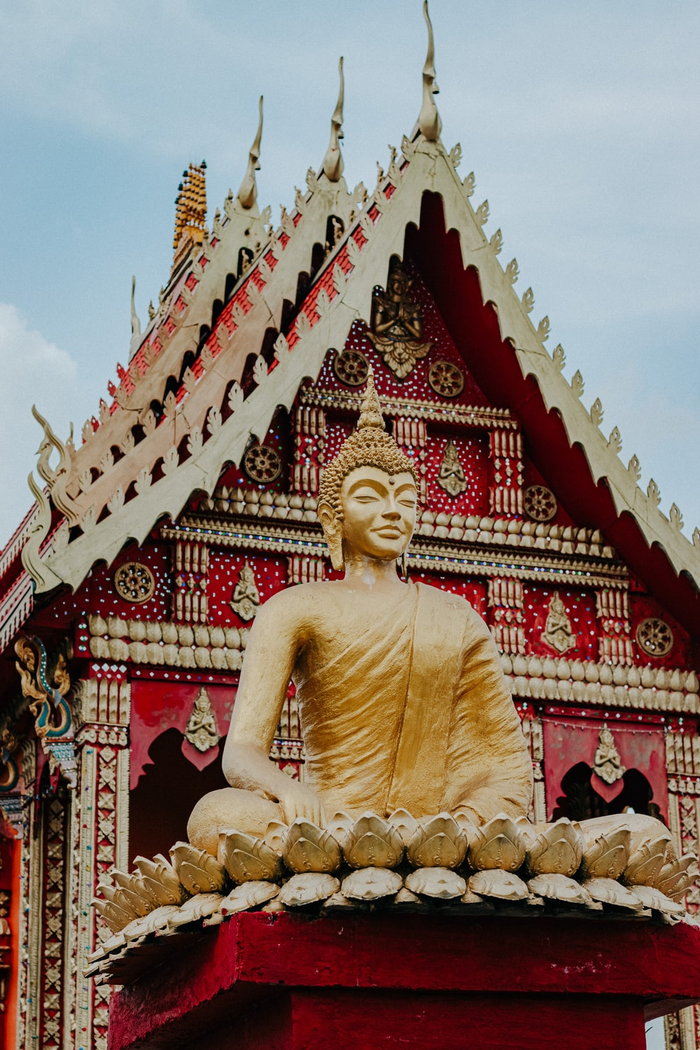 gold buddha statue near red and gold temple during daytime