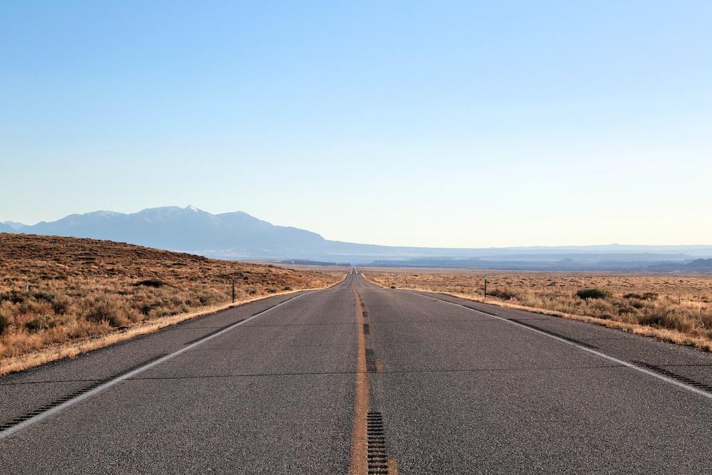 black asphalt road under blue sky during daytime