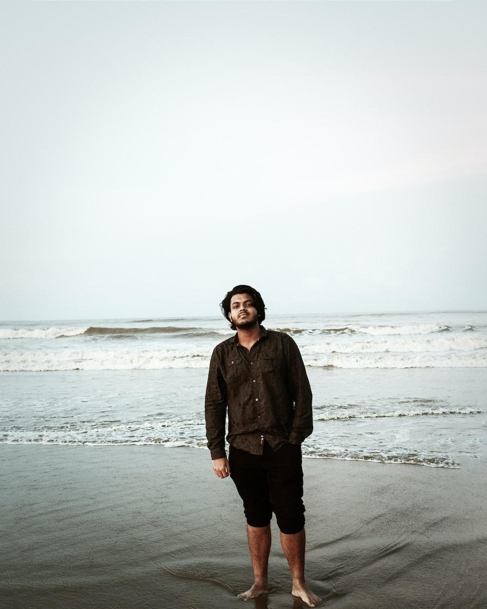 man in black jacket standing on beach