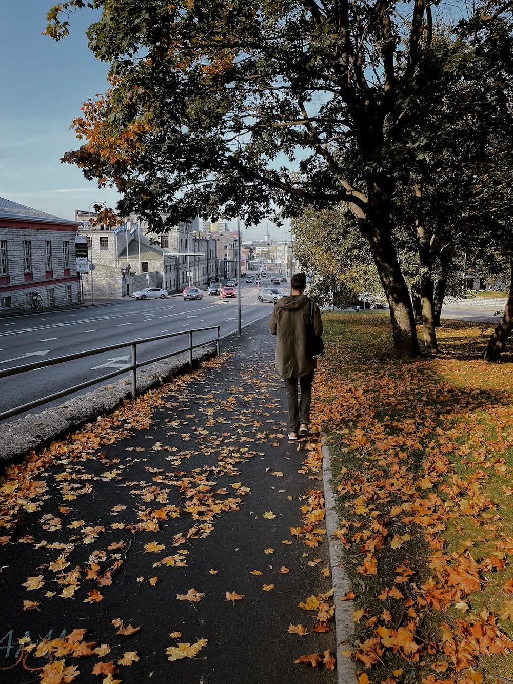 woman in brown coat walking on sidewalk during daytime