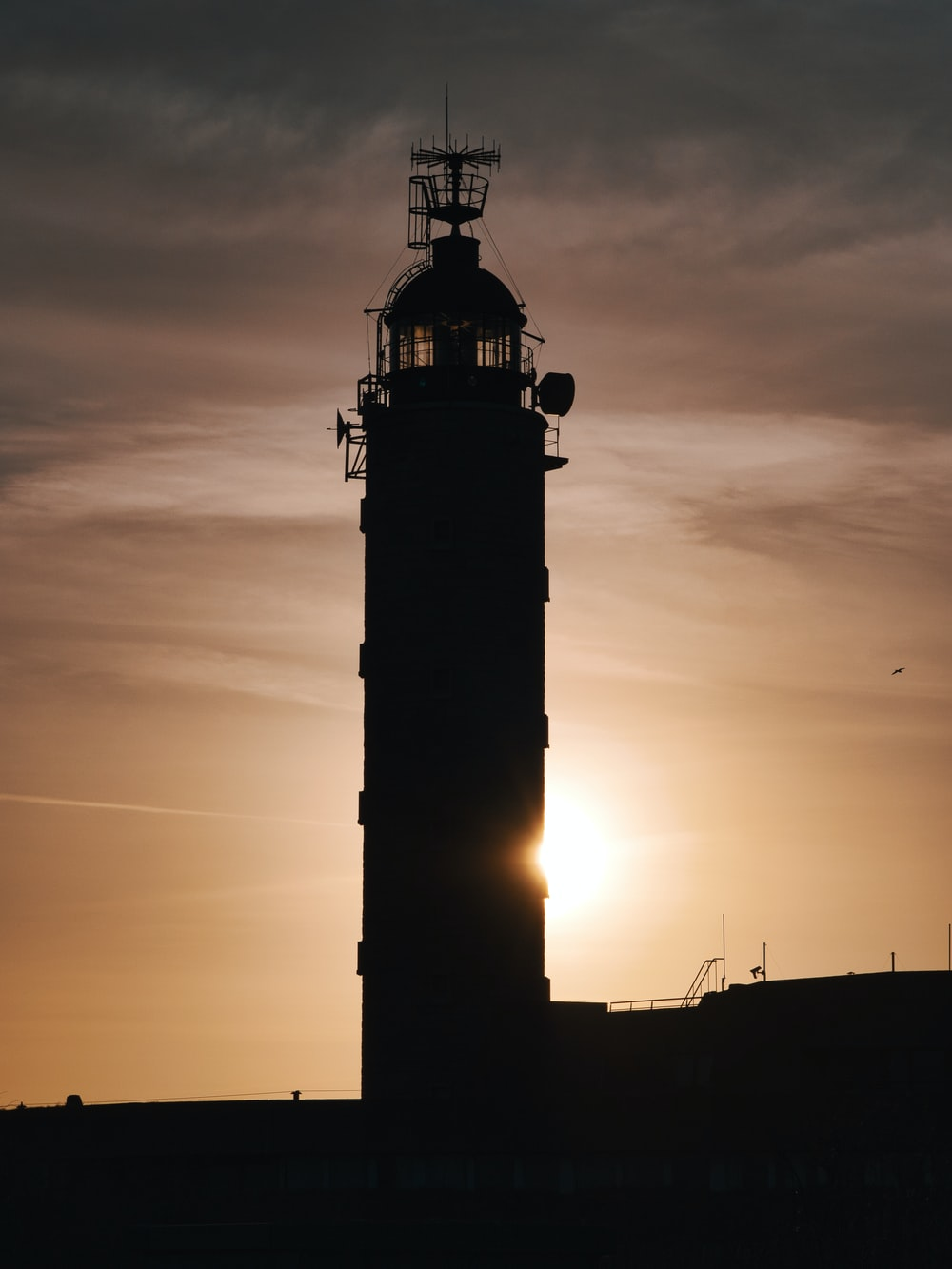 silhouette of a lighthouse during sunset