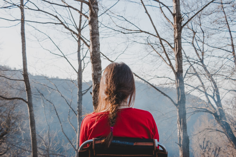 woman in red shirt standing near bare tree during daytime