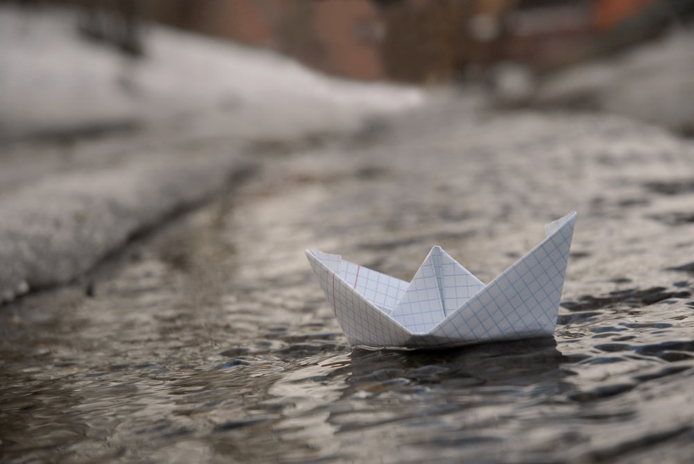 white paper boat on water