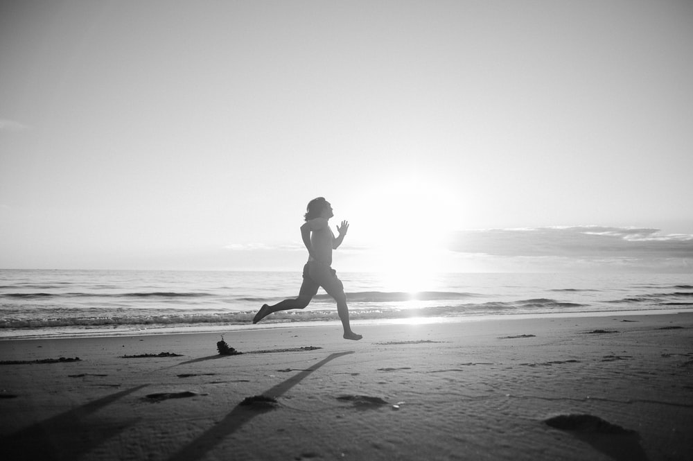 silhouette of woman walking on beach during daytime