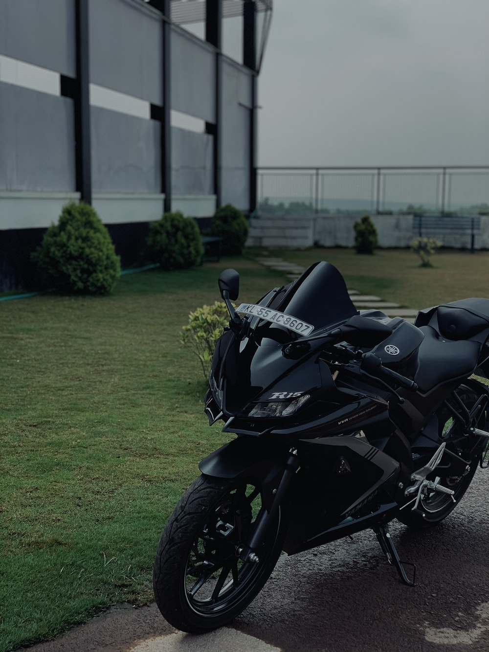 black sports bike parked on green grass field during daytime