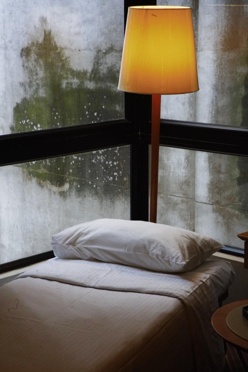 white bed linen near white window curtain