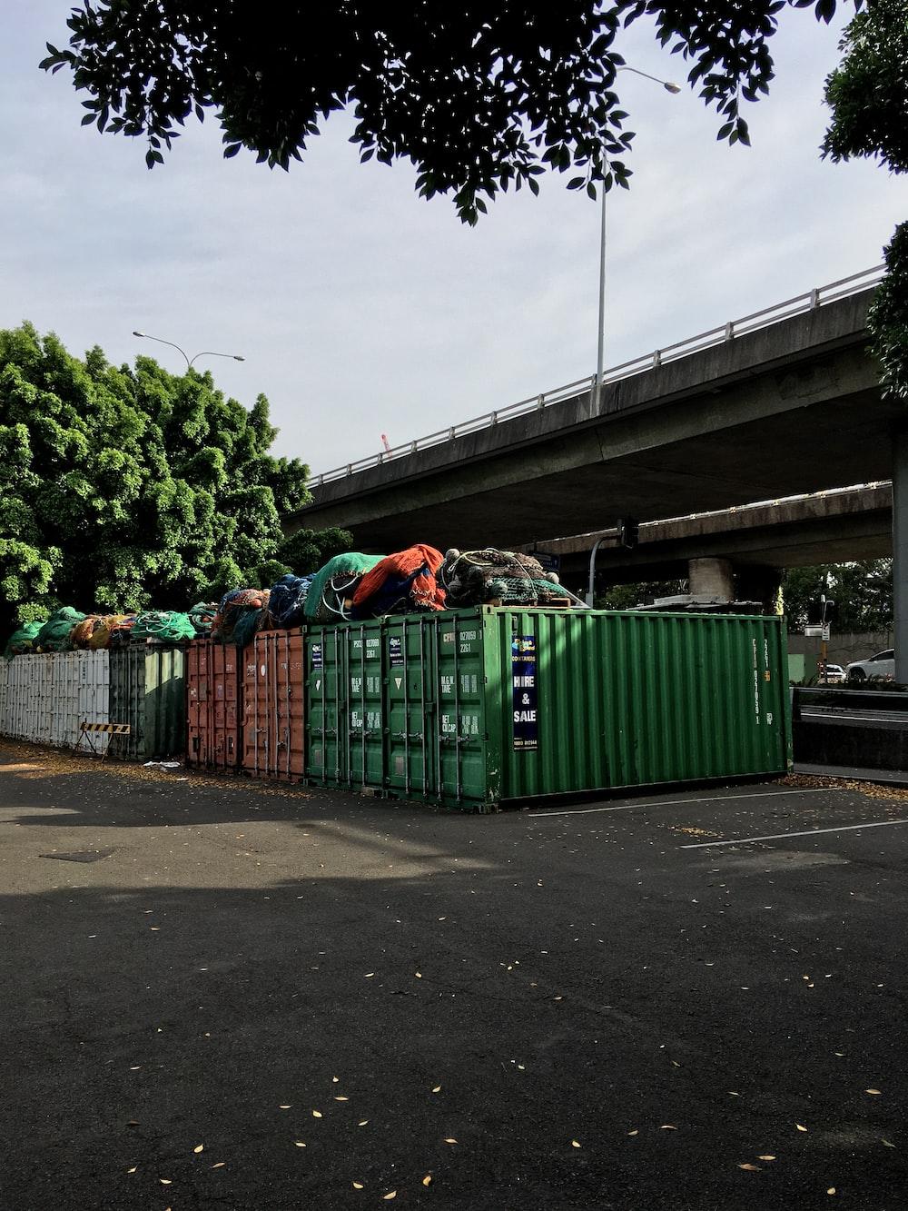 green trash bins on sidewalk during daytime