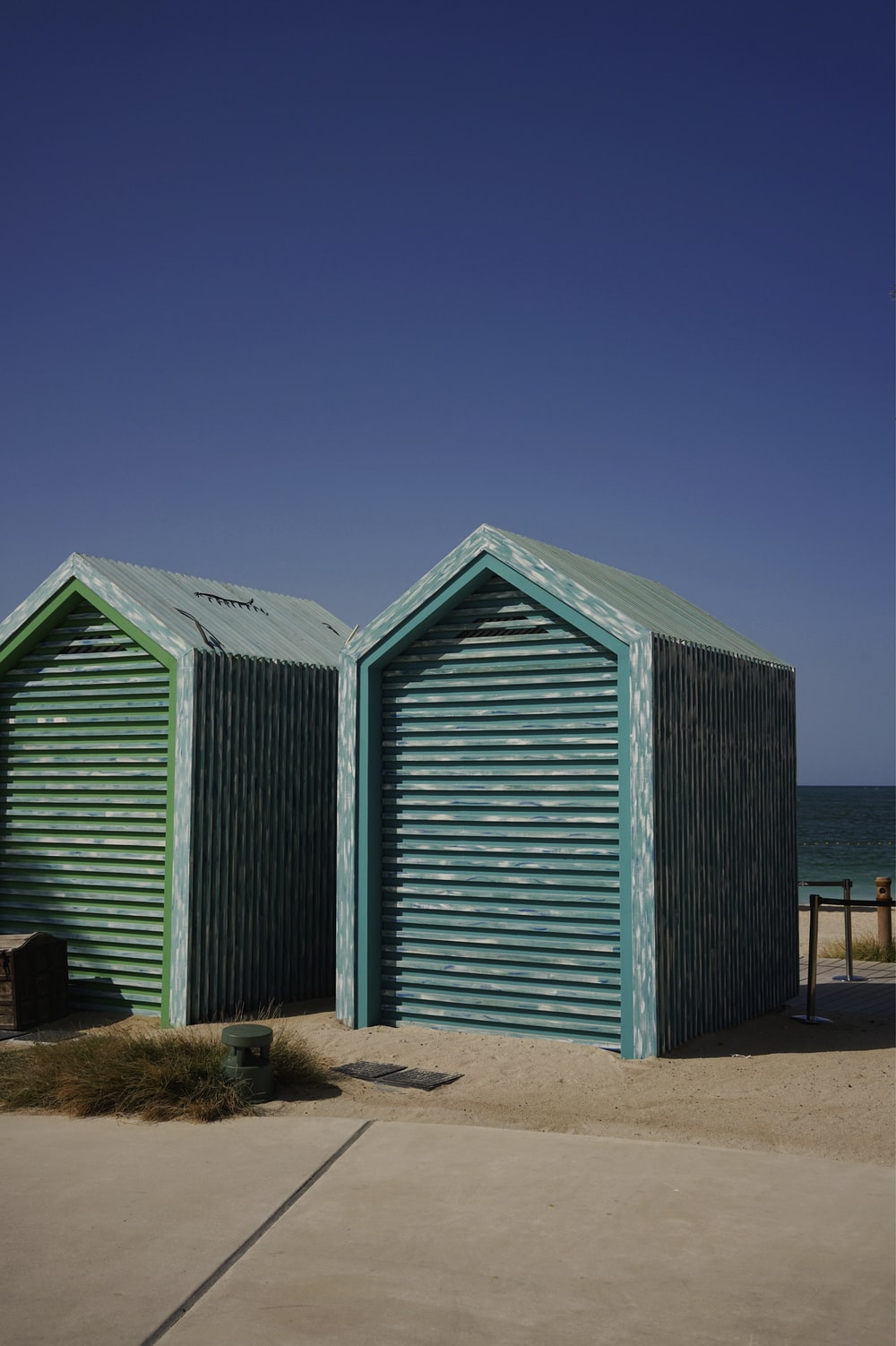 blue wooden houses on brown sand during daytime