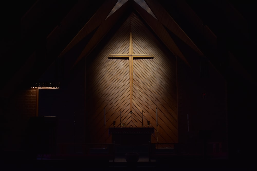 brown wooden cross on brown wooden wall
