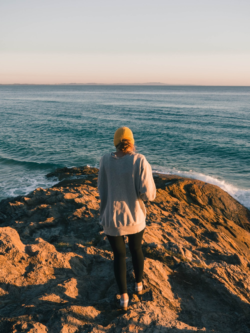 woman in gray hoodie standing on brown rock near body of water during daytime