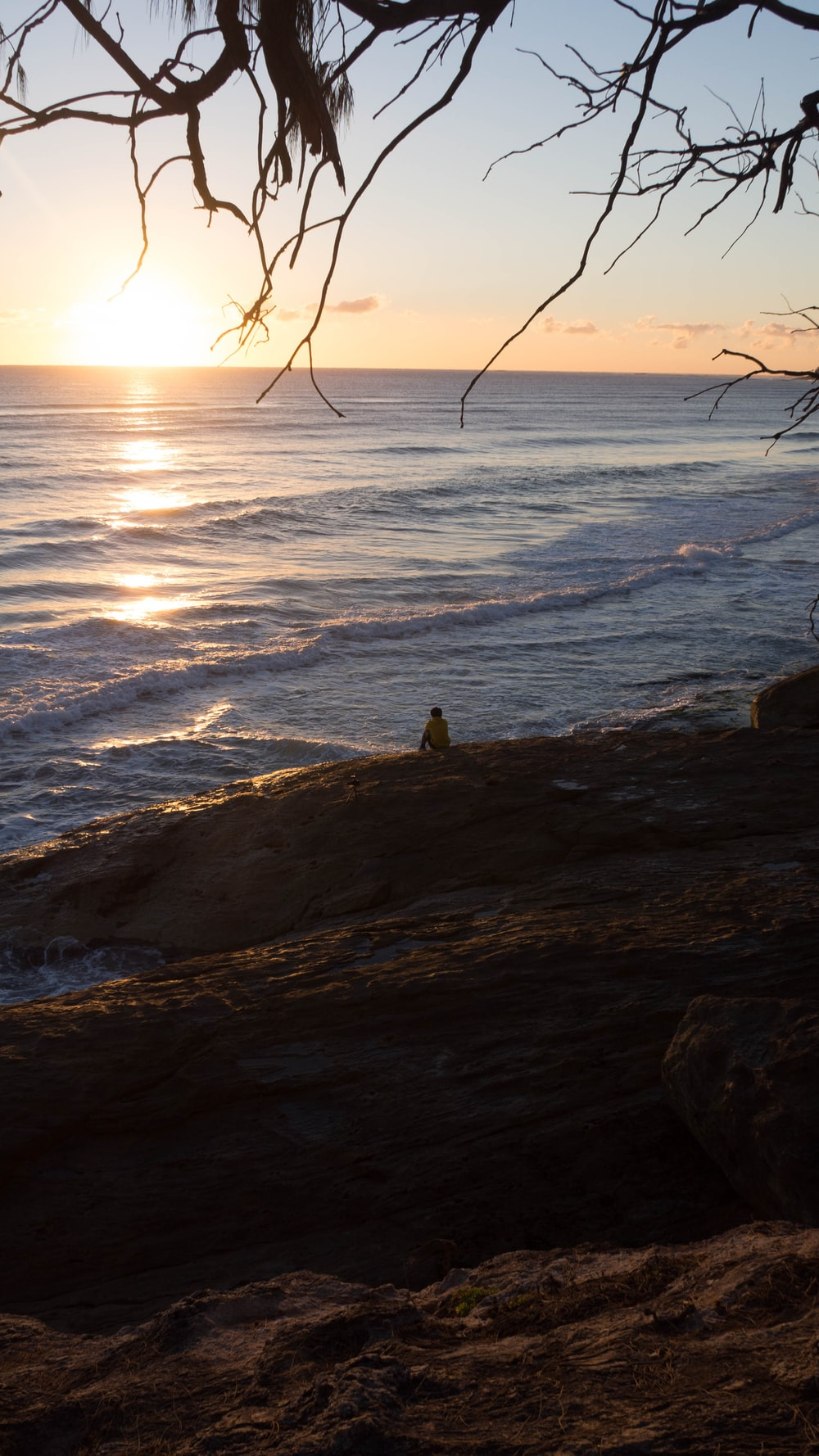 person sitting on rock near sea during daytime