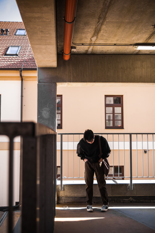 man in black jacket and black pants standing on hallway