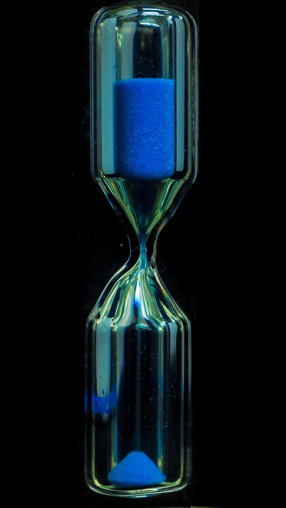 clear glass hour glass with blue liquid