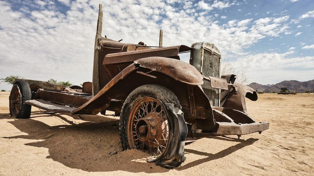 brown and black vintage car on brown sand during daytime
