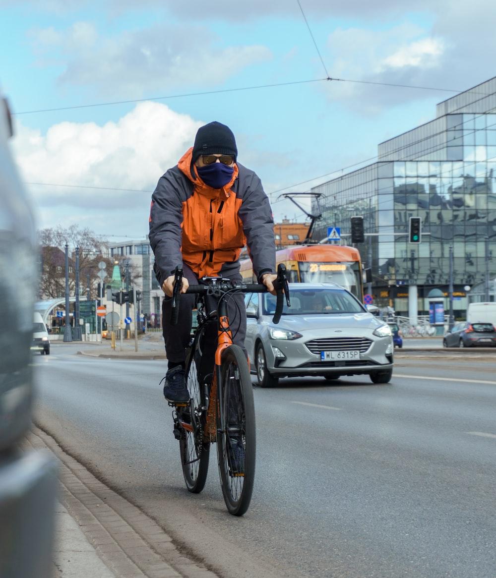 man in orange jacket riding bicycle on road during daytime