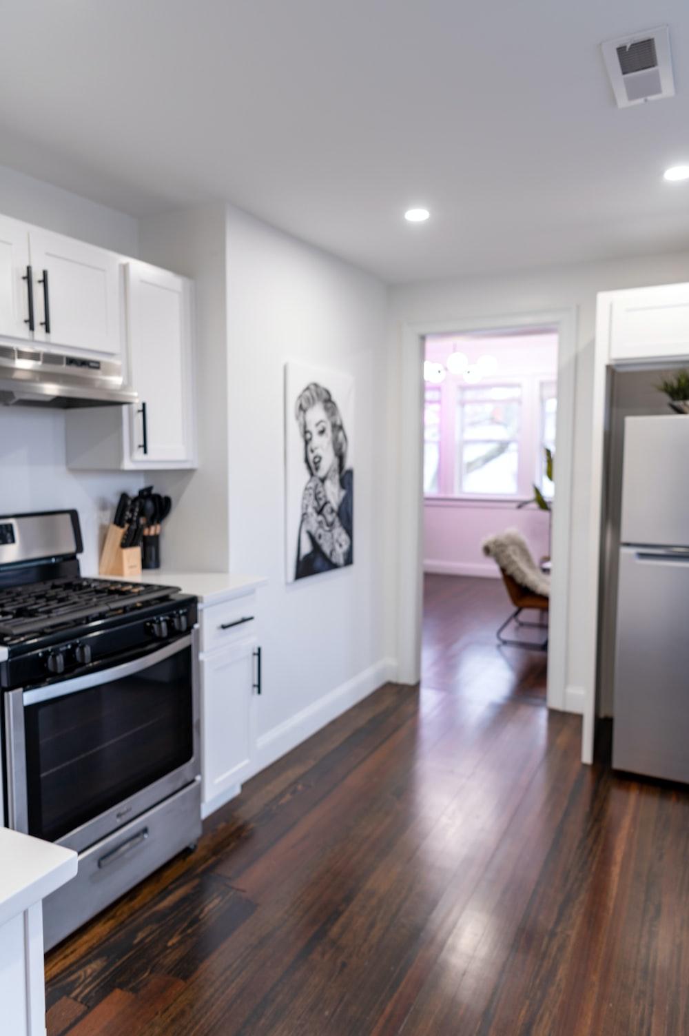white top mount refrigerator beside white wooden kitchen cabinet