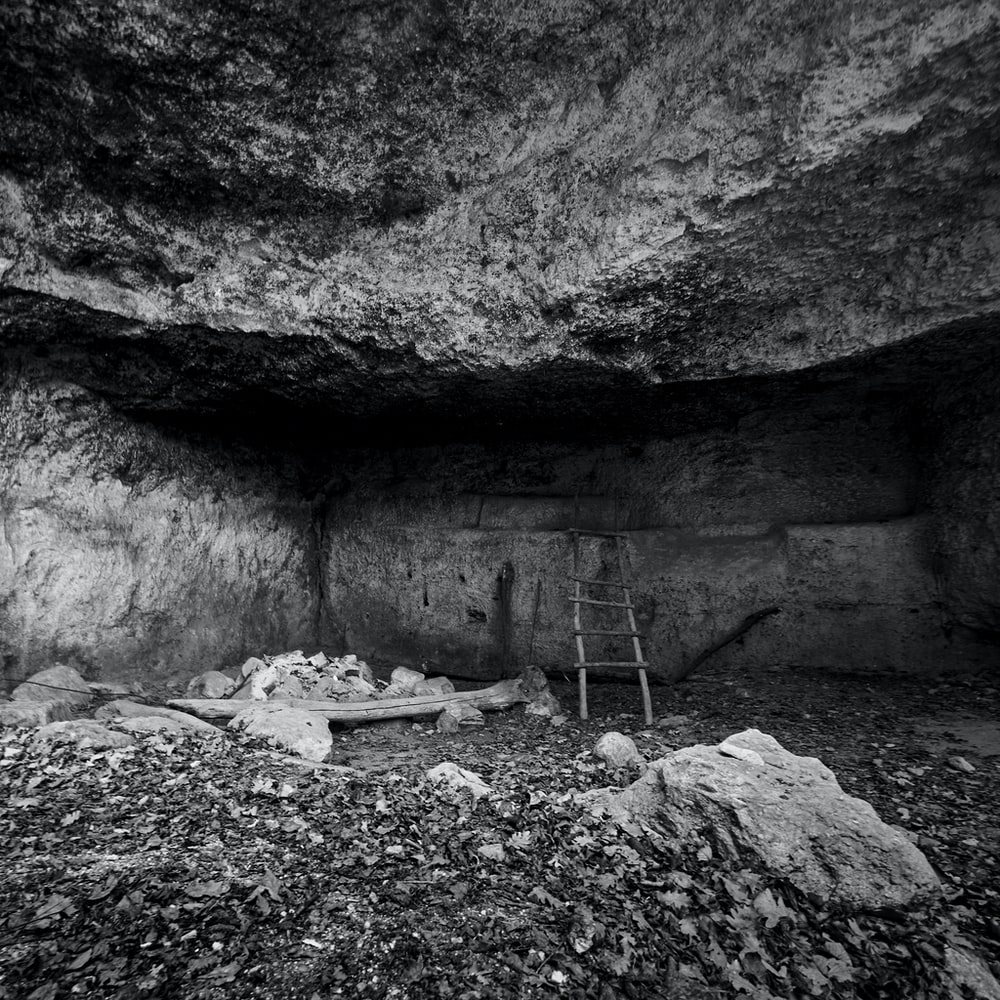 grayscale photo of person in cave